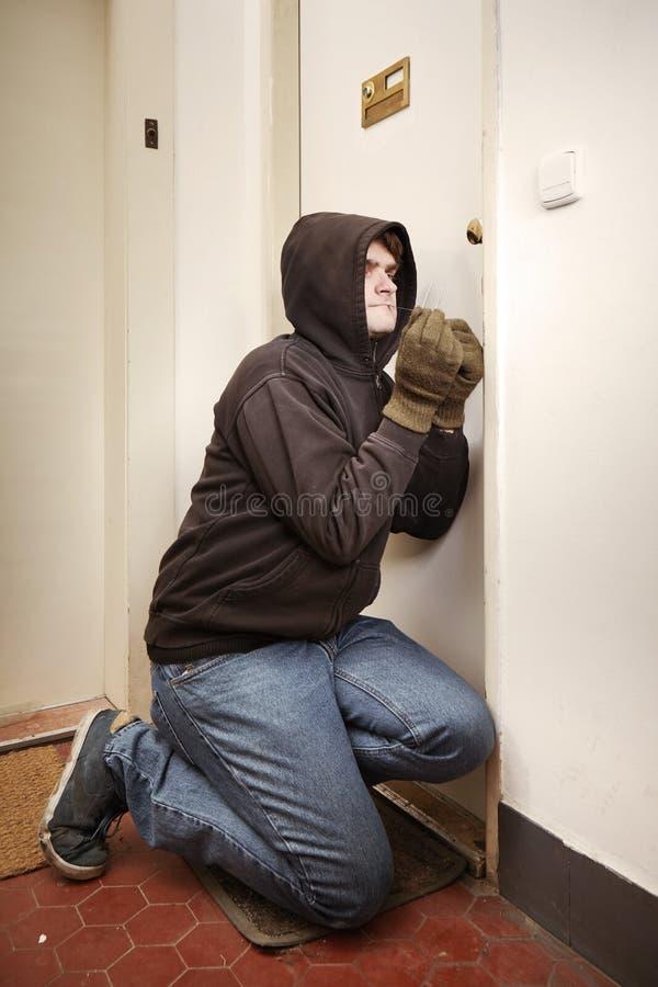Ladro in maglia con cappuccio nera che irrompe proprietà con gli strumenti casalinghi del lockpick di plastica immagine stock libera da diritti
