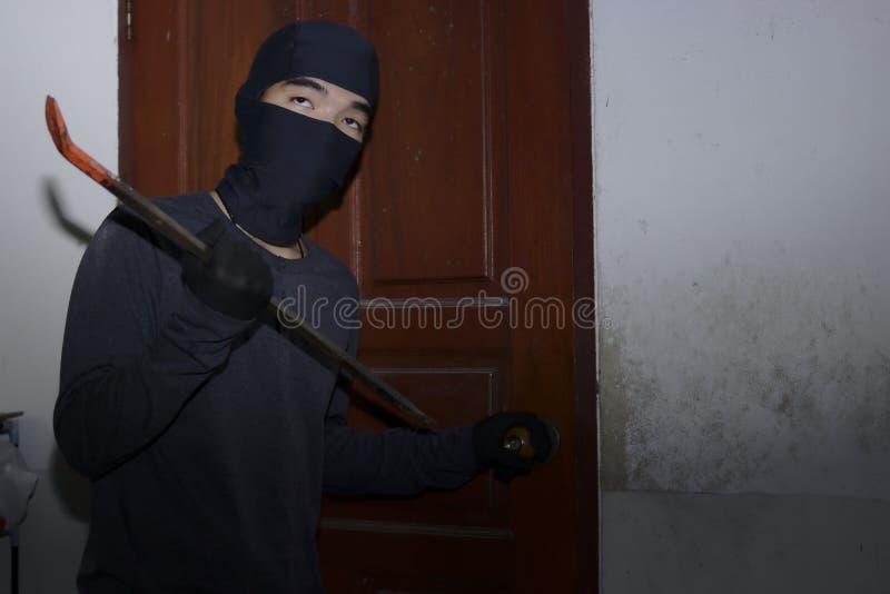 Ladro mascherato con la passamontagna facendo uso del bastone a leva alla rottura in una casa alla notte Concetto di crimine immagine stock