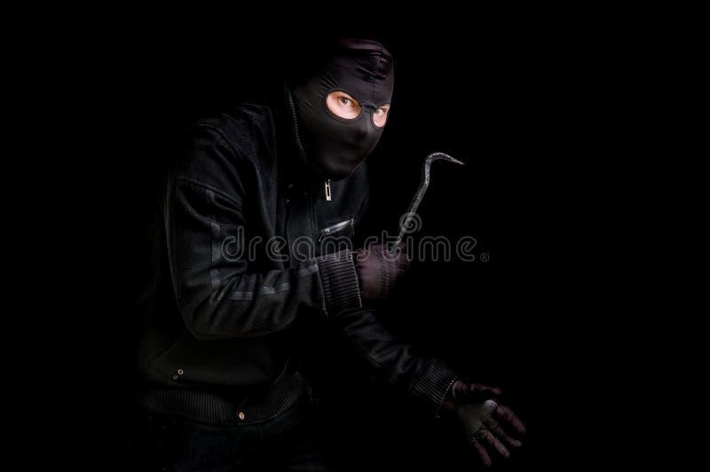 Ladro mascherato in passamontagna con il bastone a leva isolato sul nero immagine stock libera da diritti