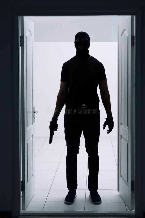 Ladro maschio che entra nella stanza fotografia stock