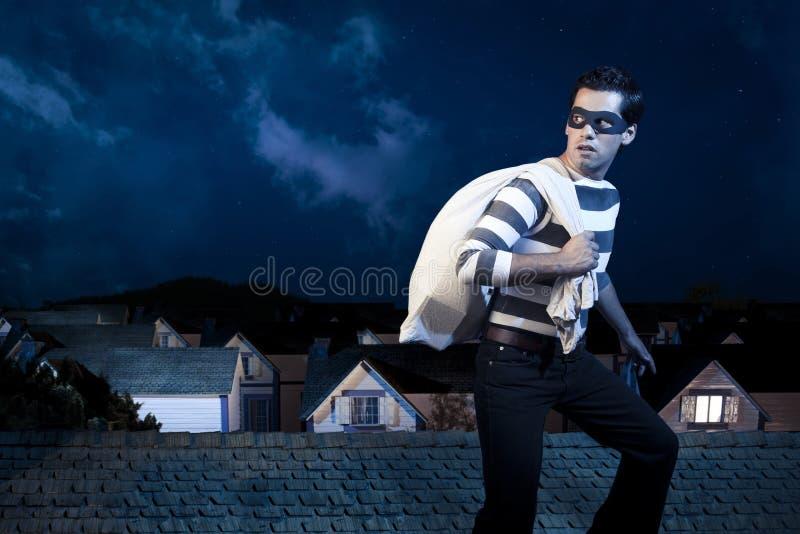 Ladro sul tetto di una casa alla notte immagine stock