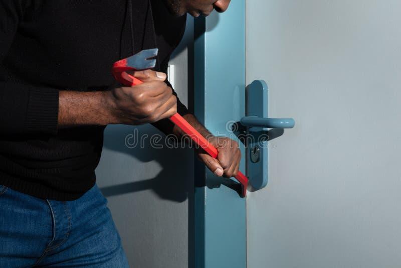 Ladro Trying To Break la porta con il bastone a leva immagini stock