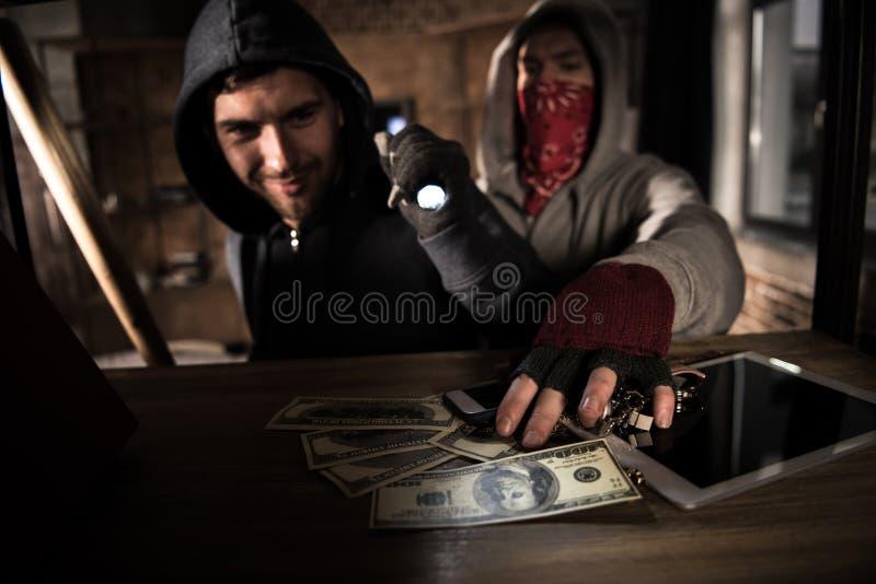 Ladrones que roban el dinero fotografía de archivo