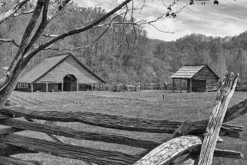 Ladugård bredvid ett plogat fält på berglantgården royaltyfri foto