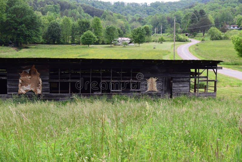 Ladugård för fam för västra NC-berg lantlig med den slingriga vägen royaltyfri bild