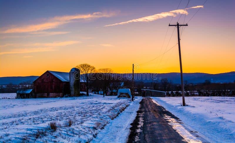Ladugården och snö täckte fält längs en landsväg i lantliga Frede fotografering för bildbyråer