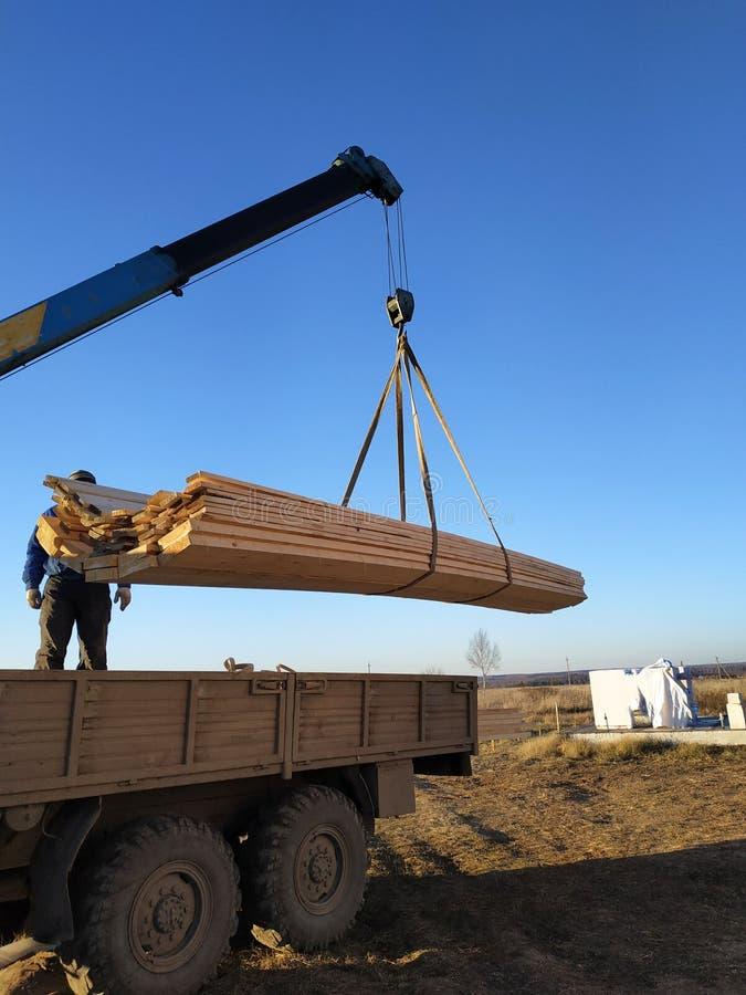 Ladungsträger geliefert an die Baustelle mit einem Kran, Manipulator lizenzfreie stockfotografie