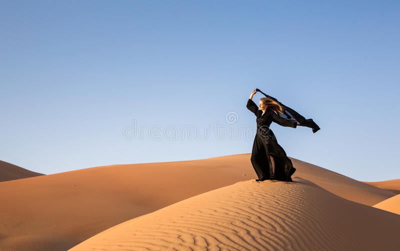 Lady in abaya in sand dunes royalty free stock images
