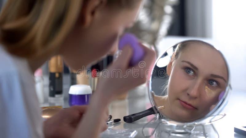Lady applying face foundation cream, correcting black circles under eyes, makeup stock photography