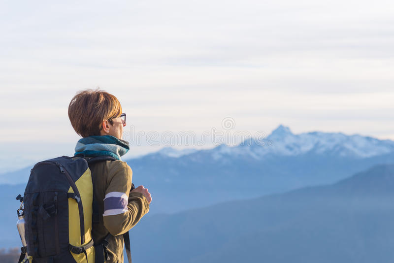 Lady with backpack looking at majestic panorama on the Alps royalty free stock photo