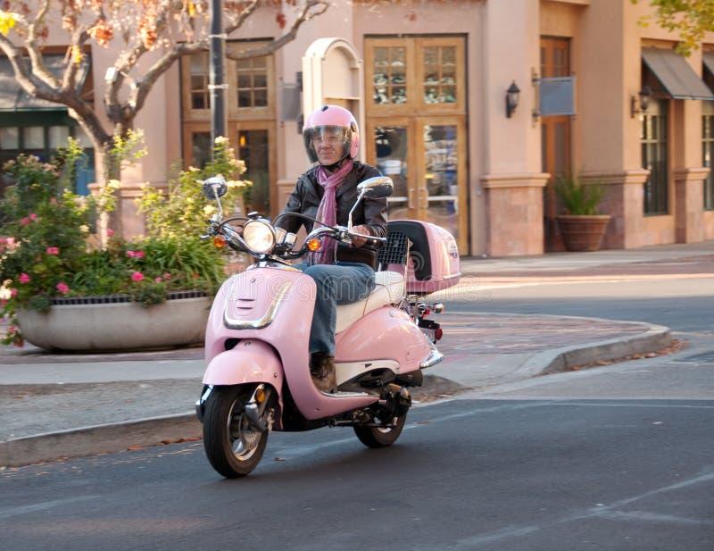 Lady biker on city street royalty free stock image
