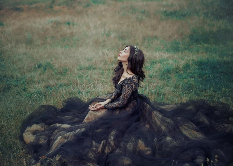 lady in black elegant dress sits on green grass. eyes closed, enjoys nature. stock images