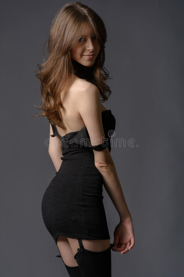 Lady in black. Torso of slim girl in a collar, in a short black dress and black stockings garters royalty free stock photography