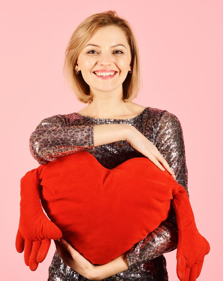 Lady with blond hair puts her arms around toy heart. royalty free stock photo