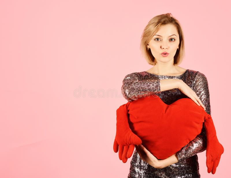 Lady with blond hair puts her arms around toy heart. stock photography