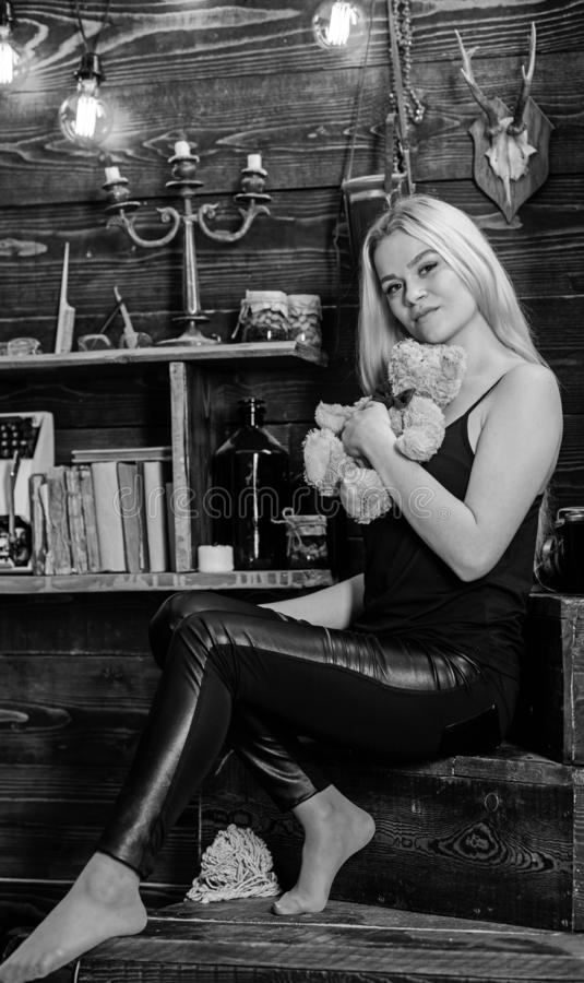 Lady blonde enjoy leisure with teddy bear. Woman on dreamy face relaxing in wooden interior. Rest and relax concept. Girl in black clothes holds teddy bear toy stock images