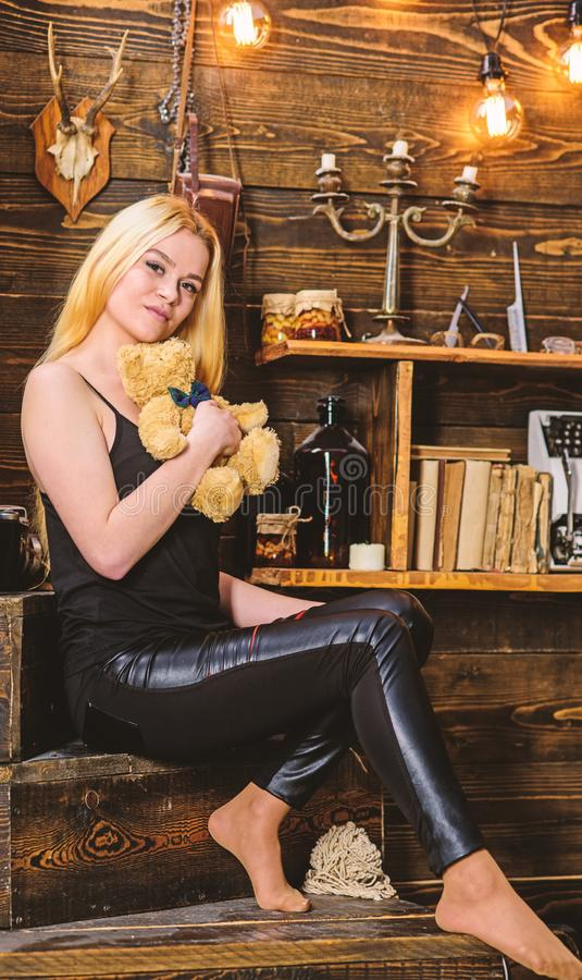 Lady blonde enjoy leisure with teddy bear. Woman on dreamy face relaxing in wooden interior. Rest and relax concept. Girl in black clothes holds teddy bear toy stock photography