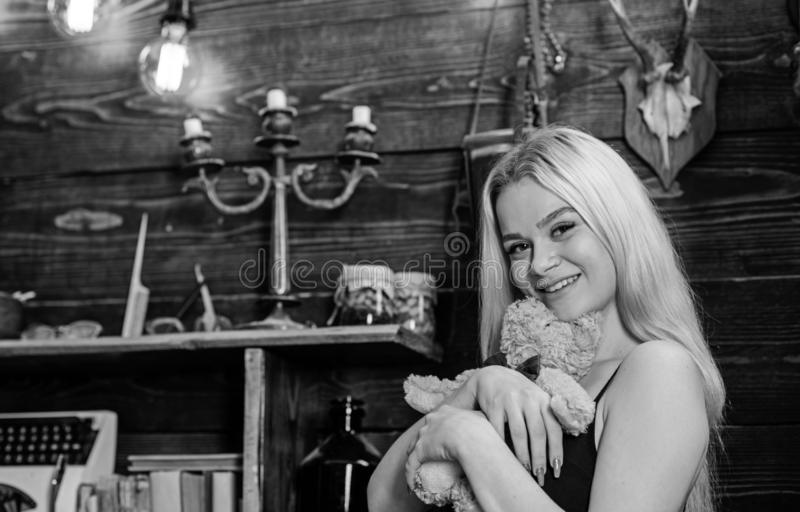 Lady blonde enjoy leisure with teddy bear. Woman on smiling face relaxing in wooden interior. Rest and relax concept. Girl in black clothes hugs teddy bear toy royalty free stock images