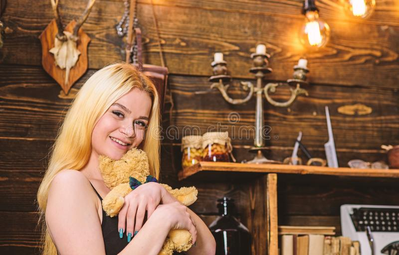 Lady blonde enjoy leisure with teddy bear. Woman on smiling face relaxing in wooden interior. Rest and relax concept. Girl in black clothes hugs teddy bear toy stock photo