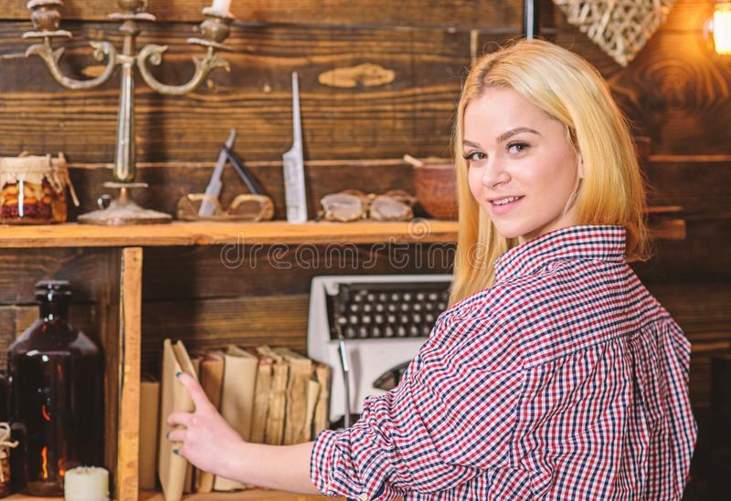 Lady blonde in plaid clothes taking book from bookshelf. Home library concept. Girl looking for book in house of. Gamekeeper. Girl in casual outfit in wooden royalty free stock photo