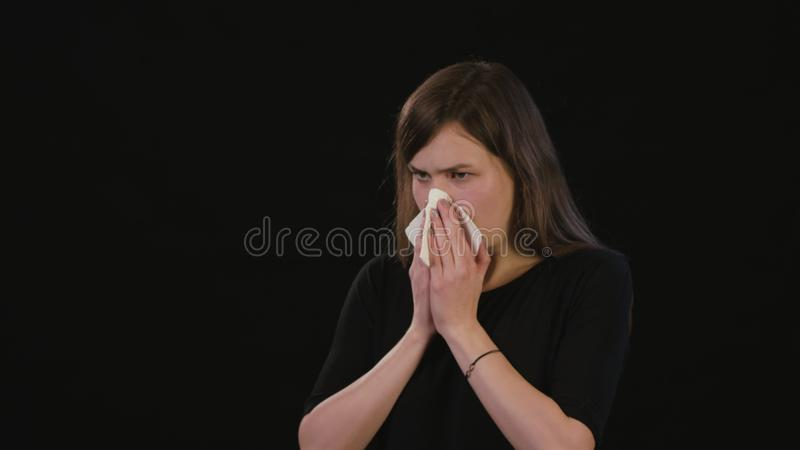 A Lady Blowing Her Nose Against a Black Background royalty free stock images
