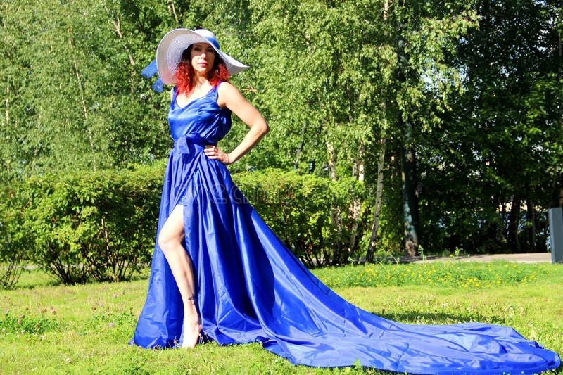 A lady in a blue dress and a white hat on a green lawn. a woman in a hat and a long dress with a train on the skirt in stock image