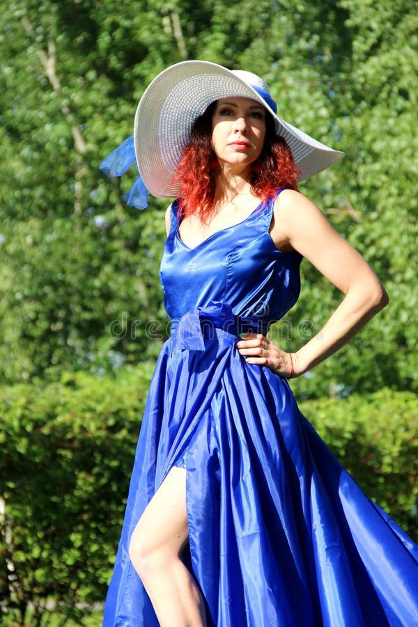 a lady in a blue dress and a white hat on a green lawn. a woman in a hat and a long dress with a train on the skirt in the Park, stock images