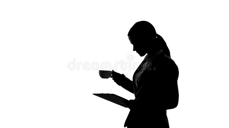 Lady boss drinking coffee, reading documents, making important business decision stock image