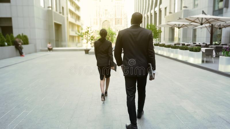 Lady boss walking by office building followed by male bodyguard, back view. Stock photo royalty free stock photography