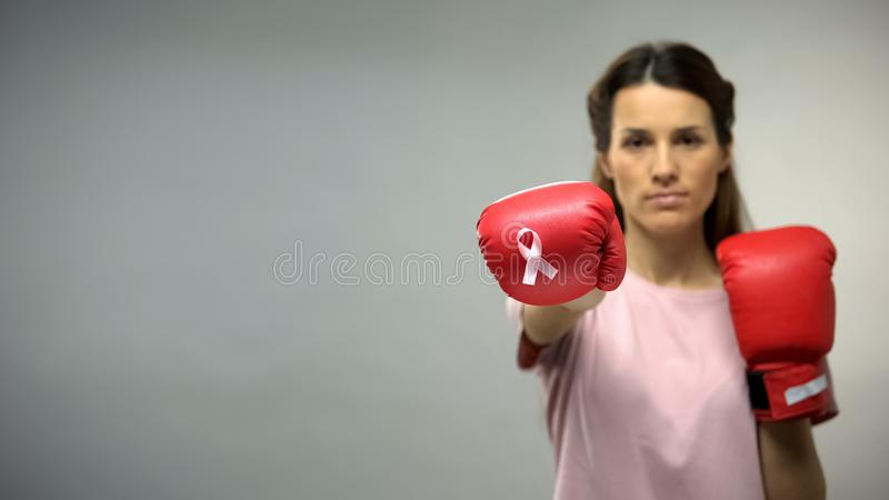 Lady in boxing gloves with pink ribbon, fighting breast cancer, social awareness royalty free stock photos