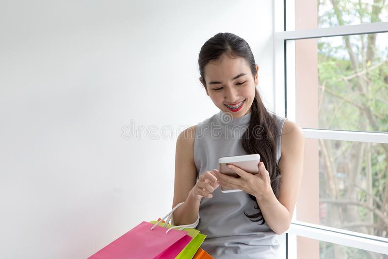 Lady buying online with a smart phone. Happy woman paying in coffee shop by smartphone. royalty free stock images