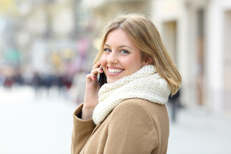 Lady calling on mobile phone and looking at you in winter royalty free stock photos
