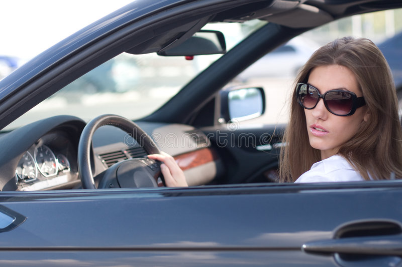 Lady in car. Portrait of elegant modern woman sitting in luxurious car royalty free stock photography