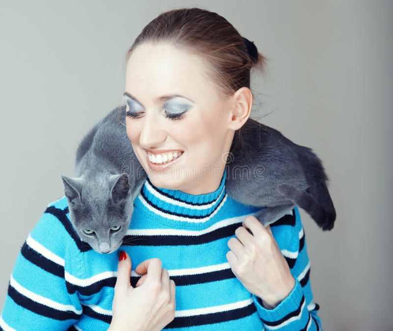 Lady and cat. Smiling lady pampering her cat indoors. Natural light and colors stock photography
