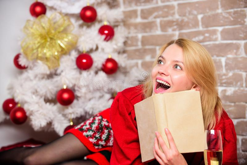 Lady celebrate christmas alone. Waiting for christmas. Girl wear red dress sit near christmas tree. Woman hold glass. Champagne and book. Winter holidays royalty free stock images