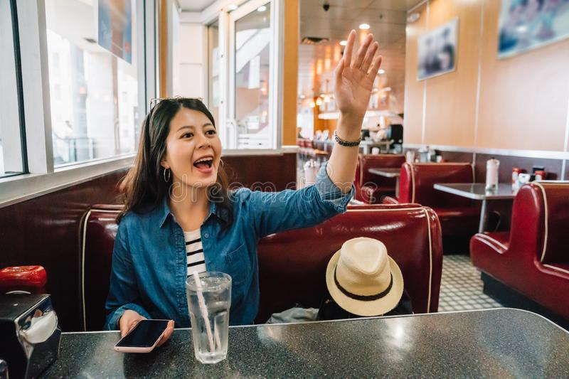 Lady cheerfully calling waiter to order food stock photography