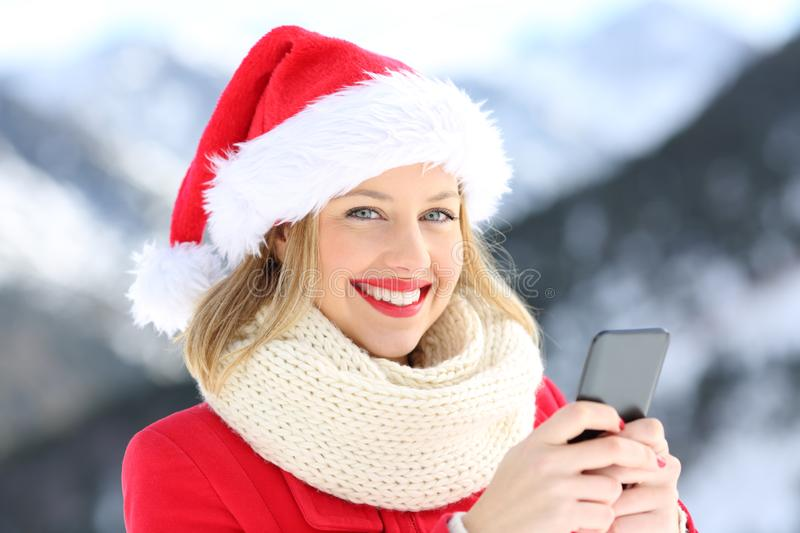 Lady on christmas holidays holding a smart phone. Portrait of a lady on christmas holidays holding a smart phone with a snowy mountain in the background royalty free stock photo