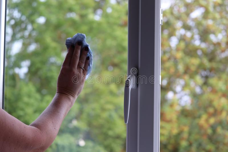 Lady cleaning the windows in a modern house stock photo