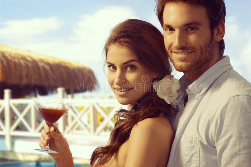 Lady with cocktail and boyfriend at tropical beach. Young casual attractive caucasian lady with cocktail drink in hand and handsome boyfriend at tropical holiday royalty free stock photography