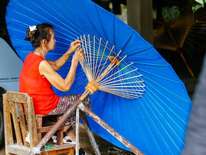 Lady crafting an Thailand Traditional Borsang Umbrella in Chiang Mai royalty free stock image