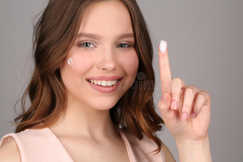 Lady with cream showing one finger. Close up. Gray background royalty free stock photos