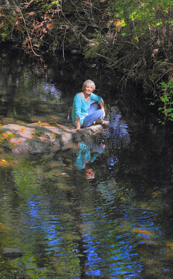 Lady by the Creek stock photo