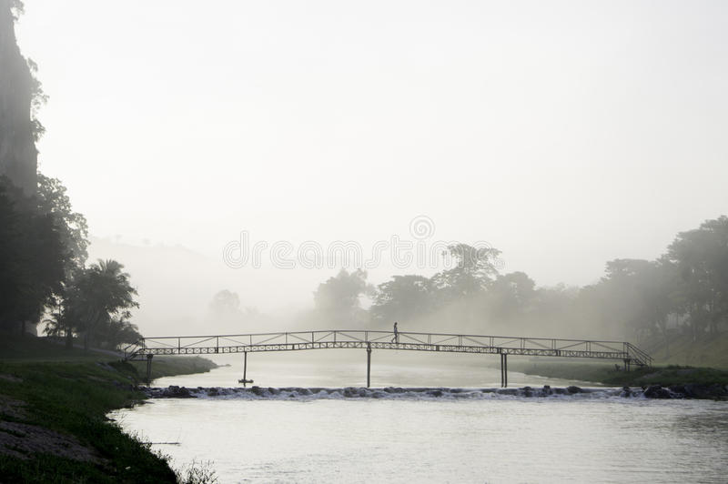 Lady crossing a bridge in the misty morning royalty free stock image