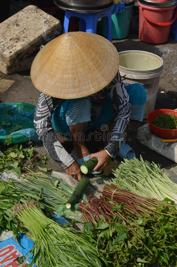 Lady cutting courgette in Can Tho food market. Vietnam - Mekong Delta- cruise along the Mekong river - Mekong River Industries - lady cutting courgette and stock image