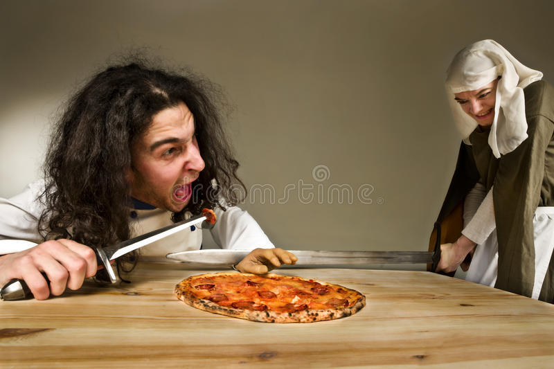 Lady cutting a hand of servant who stealing pizza. Young lady cutting the hand of gluttonous servant who stealing the pizza stock photography