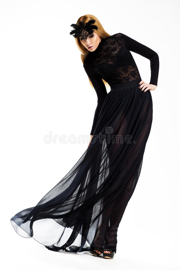 Celebration. Classy Woman dancing in Long Black Dress and Mask. Vintage Style royalty free stock photo