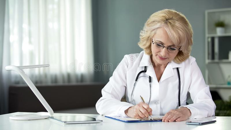 Lady doctor filling in health insurance form before proceeding to treat patient. Stock photo stock images