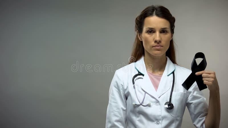 Lady doctor showing black ribbon, melanoma awareness, disease level, death rate royalty free stock images