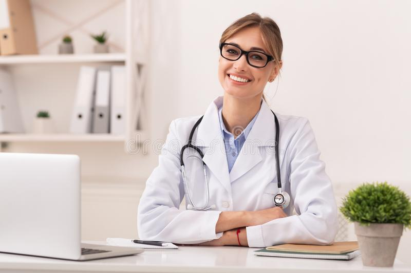 Lady Doctor Smiling At Camera Sitting In Modern Clinic Office. Family Doctor. Confident Lady Therapist Smiling At Camera Sitting In Modern Clinic Office royalty free stock photography