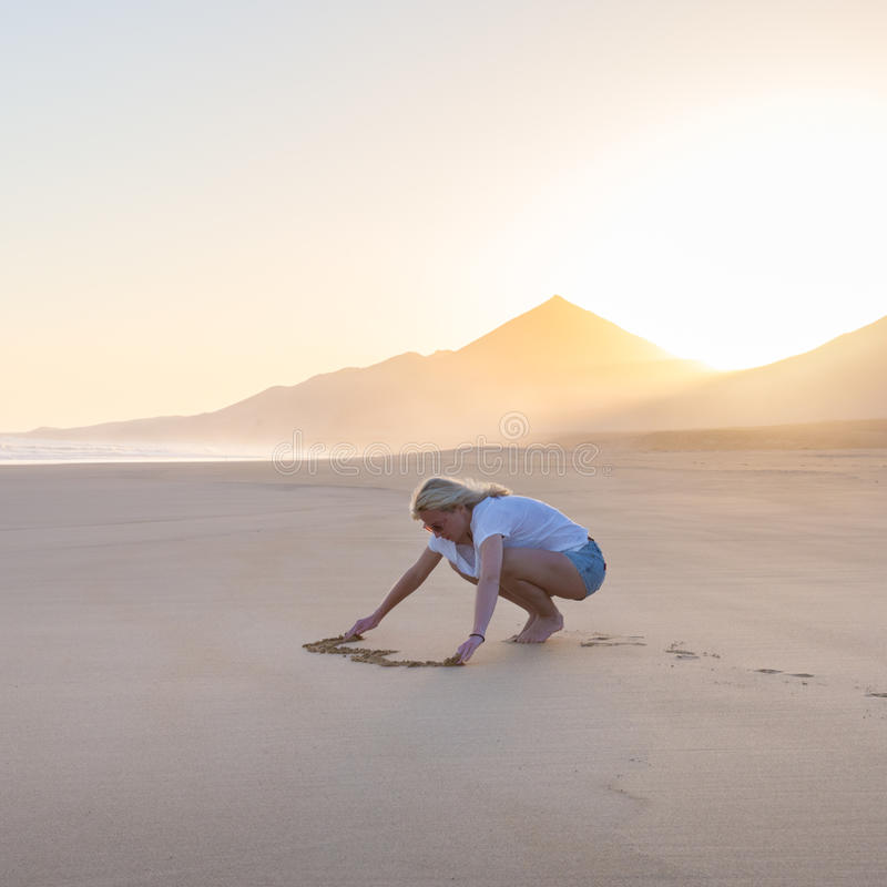Lady drawing heart shape in sand on beach. Woman drawing heart in sand on beautiful solitary Cofete beach in sunset. Love, travel concept. Fuerteventura, Canary royalty free stock image